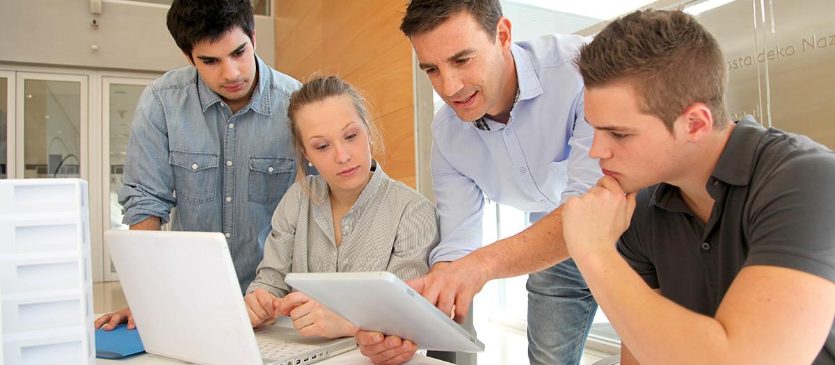 Henkilöt keskustelemassa tietokoneen äärellä